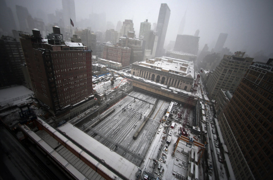 Photo - Early snowfall blankets ongoing construction of a platform for a twin tower hi-rise project, covering the Penn Station rail tracks on Tuesday, Jan. 21, 2014 in New York.  Weather forecast calls for snow through mid-afternoon with temperatures steady in the low 20s. (AP Photo/Bebeto Matthews)