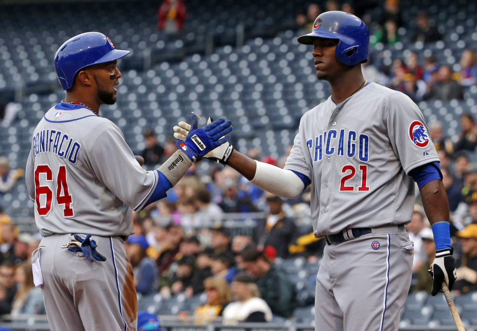 Photo - Chicago Cubs' Emilio Bonifacio (64) is greeted by teammate Junior Lake (21) after scoring on a single by Anthony Rizzo during the first inning of a baseball game against the Pittsburgh Pirates in Pittsburgh, Thursday, April 3, 2014. (AP Photo/Gene J. Puskar)