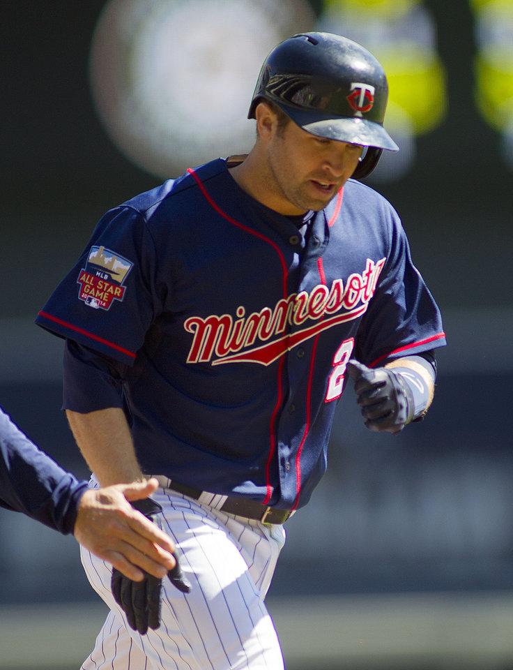 Photo - Minnesota Twins second baseman Brian Dozier (2) is congratulated after hitting a home run against Oakland Athletics in the first inning of their baseball game on Thursday, April 10, 2014 in Minneapolis.(AP Photo/Andy Clayton-King)