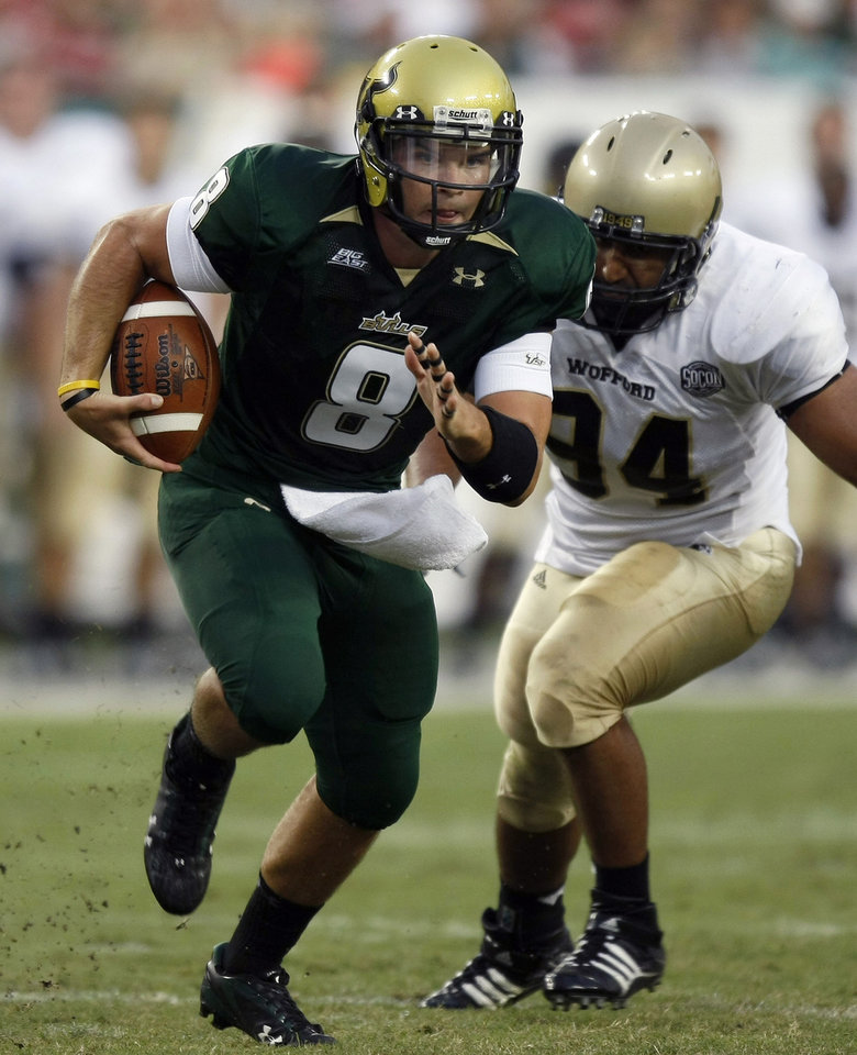 Photo - South Florida quarterback Matt Grothe (8) scrambles away from Wofford's Ameet Pall (94) during the first quarter of an NCAA college football game Saturday, Sept. 5, 2009, in Tampa, Fla. (AP Photo/Chris O'Meara) ORG XMIT: TPS103