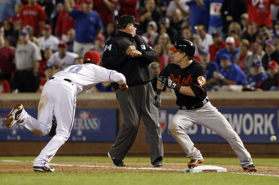 Photo -   A throwing error by Texas Rangers pitcher Derek Holland gets past Michael Young (10), allowing Baltimore Orioles' Nate McLouth to advance to second during the seventh inning of an American League wild-card playoff baseball game Friday, Oct. 5, 2012, in Arlington, Texas. (AP Photo/LM Otero)
