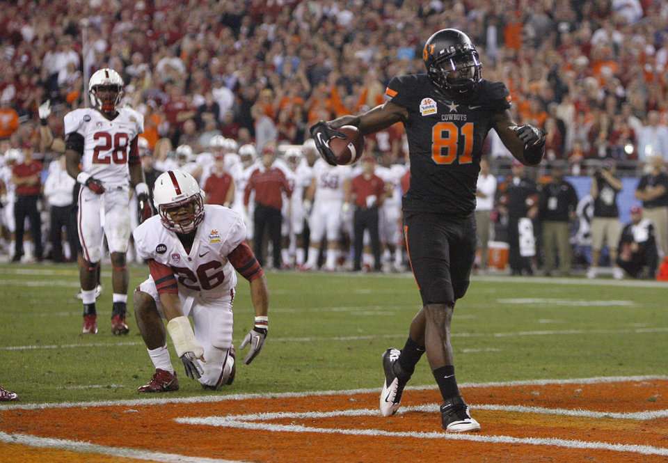 Photo - Oklahoma State's Justin Blackmon (81) celebrates in front of Stanford's Delano Howell (26) and Harold Bernard (28) during the Fiesta Bowl between the Oklahoma State University Cowboys (OSU) and the Stanford Cardinal at the University of Phoenix Stadium in Glendale, Ariz., Monday, Jan. 2, 2012. Photo by Sarah Phipps, The Oklahoman