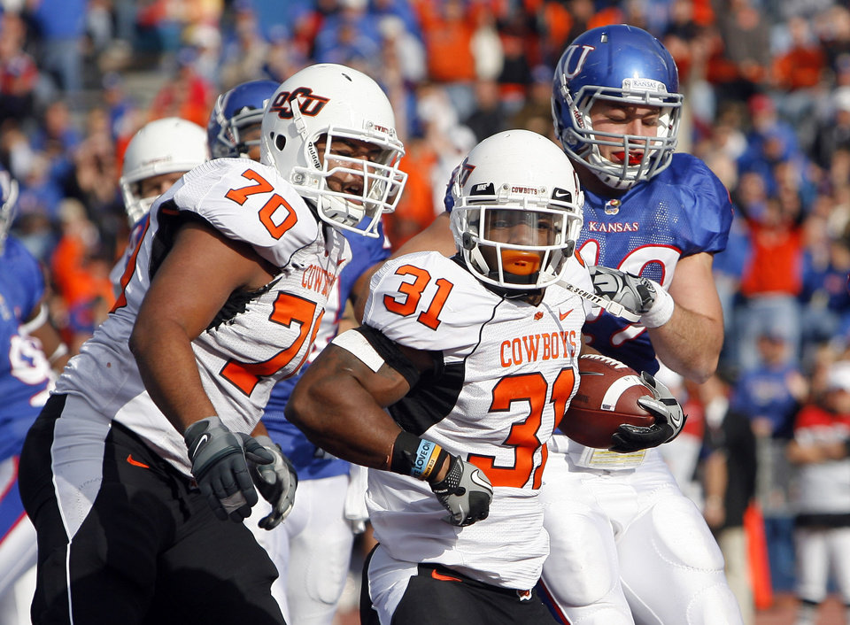 Photo - Oklahoma State's Jeremy Smith (31) scores a touchdown in front Kansas' Drew Dudley (49) as Oklahoma State's Jonathan Rush (70) blocks during the college football game between Oklahoma State (OSU) and Kansas (KU), Saturday, Nov. 20, 2010 at Memorial Stadium in Lawrence, Kan. Photo by Sarah Phipps, The Oklahoman