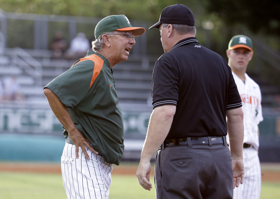 Photo - Miami head coach Jim Morris, left, urgues with first base umpire Jim Schaly, right, after Texas Tech's Devon Conley was ruled safe at first in the second inning during an NCAA college baseball regional tournament in Coral Gables, Fla., Saturday, May 31, 2014. (AP Photo/Lynne Sladky)