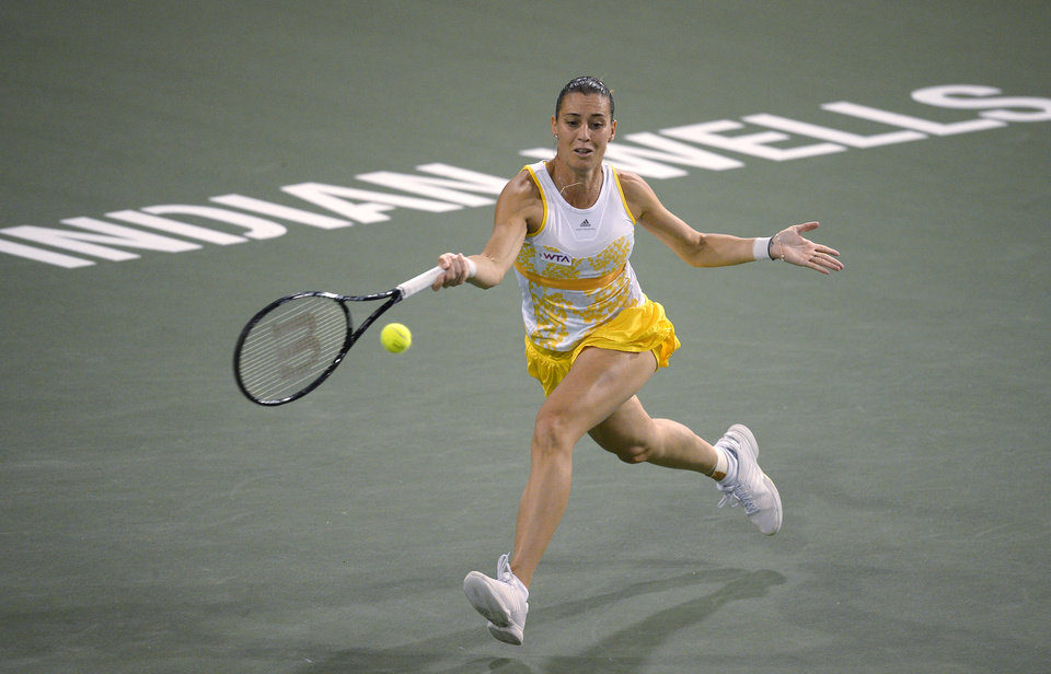 Photo - Flavia Pennetta, of Italy,  eturns a shot to Li Na, of China, at the BNP Paribas Open tennis tournament, Friday, March 14, 2014, in Indian Wells, Calif. (AP Photo/Mark J. Terrill)