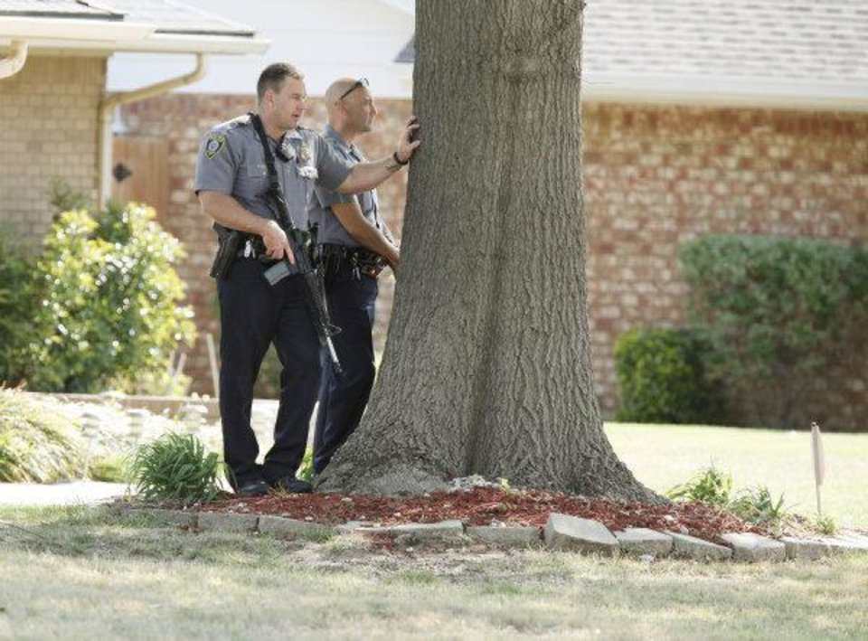 Photo - HOUSE SEARCH: Oklahoma City police take position across the street from a home in the 4100 block of NW 60th in Oklahoma City , April 13 , 2011. Photo by Steve Gooch, The Oklahoman ORG XMIT: KOD
