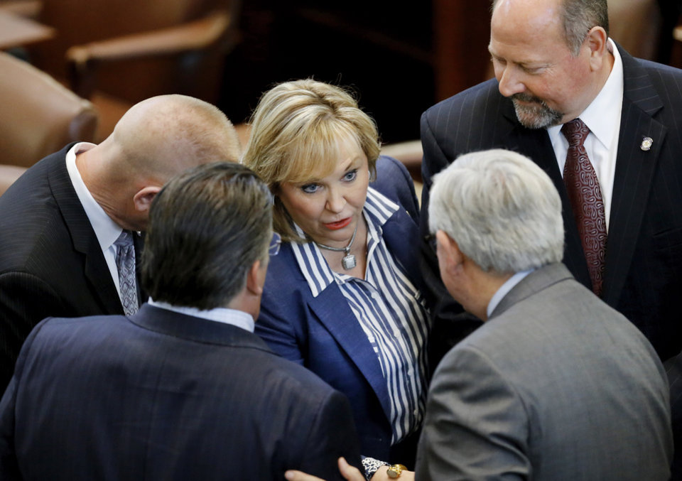 Photo -  Gov. Mary Fallin huddles with lawmakers in the House chamber on Monday. Lawmakers were voting on budget measures, including a hike to the cigarette tax, which failed. [Photo by Jim Beckel, The Oklahoman]