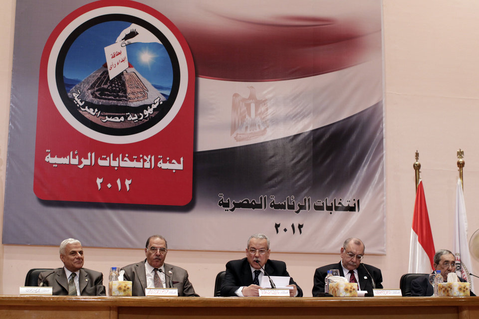 Photo -   The Egyptian special election committee announces the result in the Egyptian presidential election, at a press conference in Cairo, Egypt, Monday, May 28, 2012. From left: judge Mohamed Mommtaz, judge Abd el-Moez Ebrahim, judge and chairman Farouk Sultan, judge Maher Behery and judge Ahmed Kafagy. The chairman of Egypt's presidential election commission says the Muslim Brotherhood's candidate and Hosni Mubarak's last prime minister will context next month's runoff vote. Farouq Sultan said Monday the official final results show the Brotherhood's Mohammed Morsi and Ahmed Shafiq, a former air force commander, as the top two finishers in the first round of voting on May 23-24. He said Morsi won 5.76 million votes, while Shafiq garnered 5.5 million votes. (AP Photo/Frederik Persson)