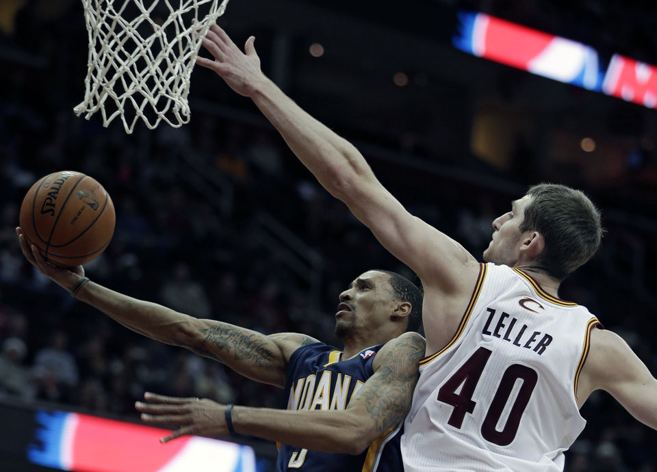 Indiana Pacers' George Hill, left, jumps to the basket against Cleveland Cavaliers' Tyler Zeller during the first quarter of an NBA basketball game on Friday, Dec. 21, 2012, in Cleveland. (AP Photo/Tony Dejak)
