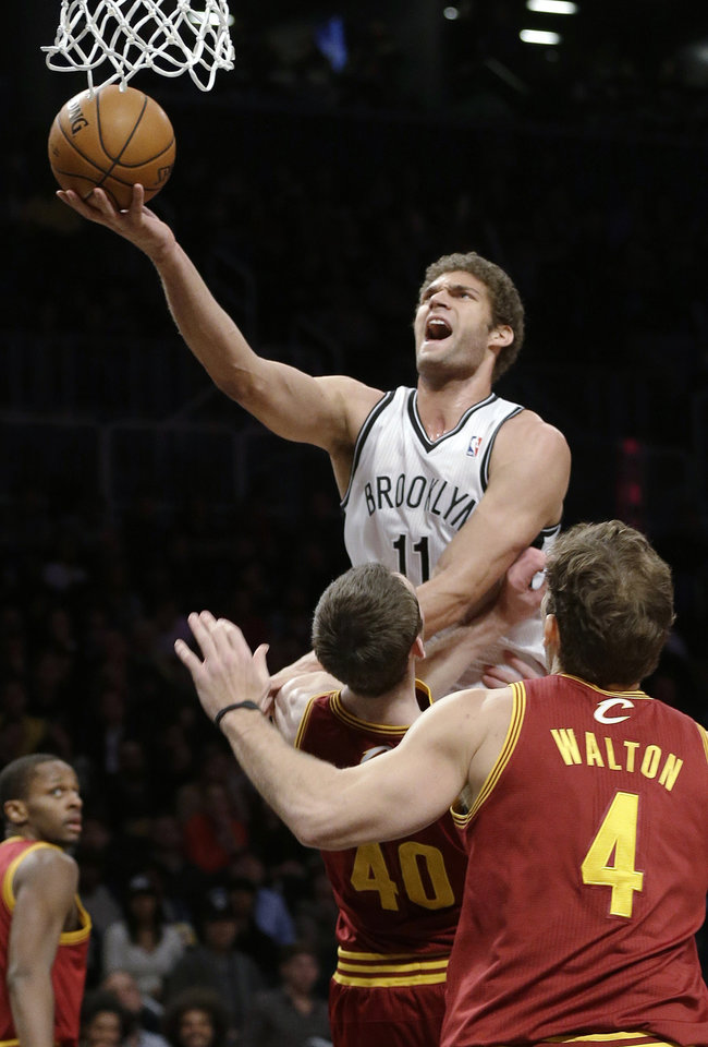 Photo - Brooklyn Nets' Brook Lopez (11) shoots over Cleveland Cavaliers' Tyler Zeller (40) during the first half of an NBA basketball game Saturday, Dec. 29, 2012, in New York. (AP Photo/Frank Franklin II)