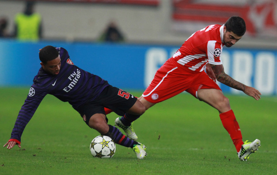 Olympiakos' Paulo Machado, right, fights for the ball with Arsenal's Jernande Meade during their group B Champions League soccer match in the port of Piraeus, near Athens, Tuesday, Dec. 4, 2012. (AP Photo/Thanassis Stavrakis)