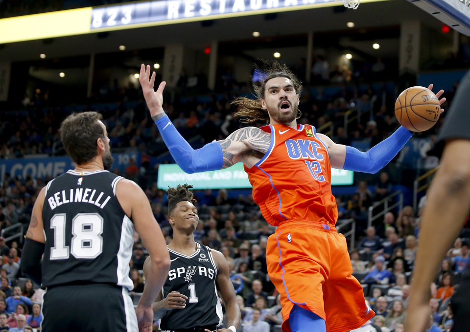 Photo - Oklahoma City's Steven Adams (12) dunks the ball beside San Antonio's Marco Belinelli (18) and Lonnie Walker IV (1) during an NBA basketball game between the Oklahoma City Thunder and the San Antonio Spurs at Chesapeake Energy Arena in Oklahoma City, Sunday, Feb. 23, 2020. Oklahoma city won 131-103. [Bryan Terry/The Oklahoman]