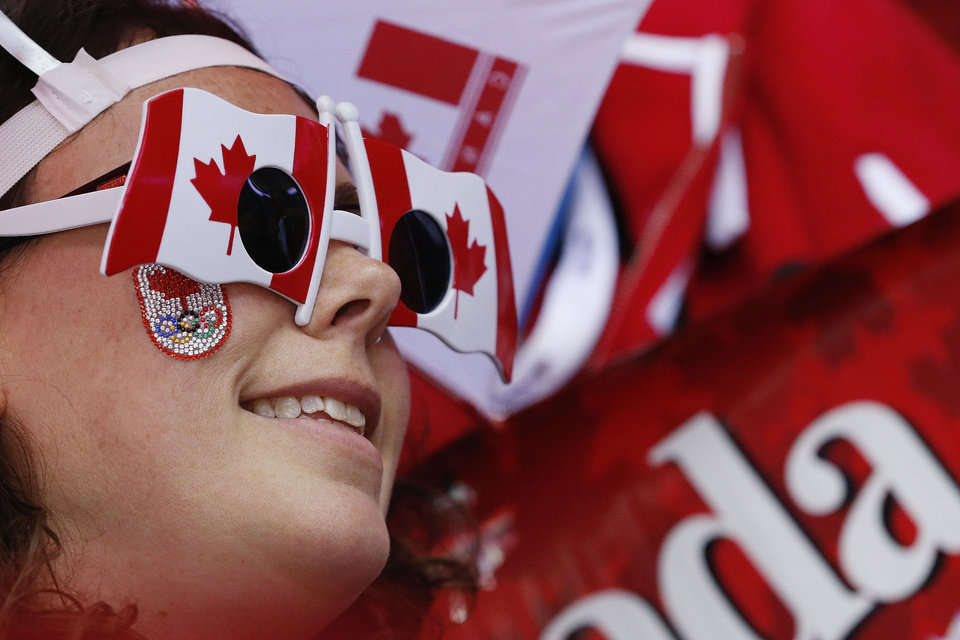 Photo - A Canadian fan watches the start of the women's gold medal ice hockey game between Canada and the United States at the 2014 Winter Olympics, Thursday, Feb. 20, 2014, in Sochi, Russia. (AP Photo/Julio Cortez)