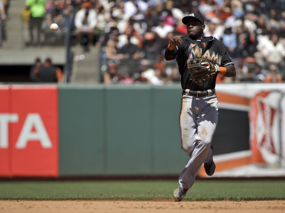 Photo - Miami Marlins shortstop Adeiny Hechavarria makes an off-balance throw to put out San Francisco Giants' Hunter Pence at first base during the fifth inning of a baseball game on Sunday, May 18, 2014, in San Francisco. (AP Photo/Marcio Jose Sanchez)