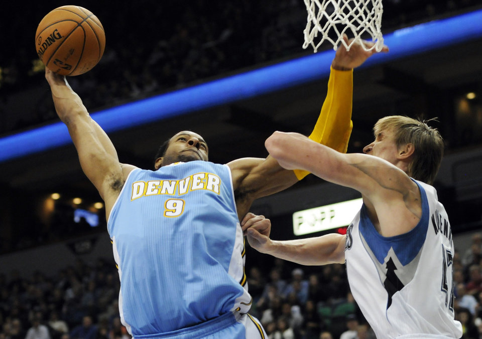 Photo -   Denver Nuggets' Andre Iguodala, left, lays up as Minnesota Timberwolves' Andrei Kirilenko, of Russia, defends in the second half of an NBA basketball game on Wednesday, Nov. 21, 2012, in Minneapolis. The Nuggets won 101-94. Iguodala scored18 points. (AP Photo/Jim Mone)