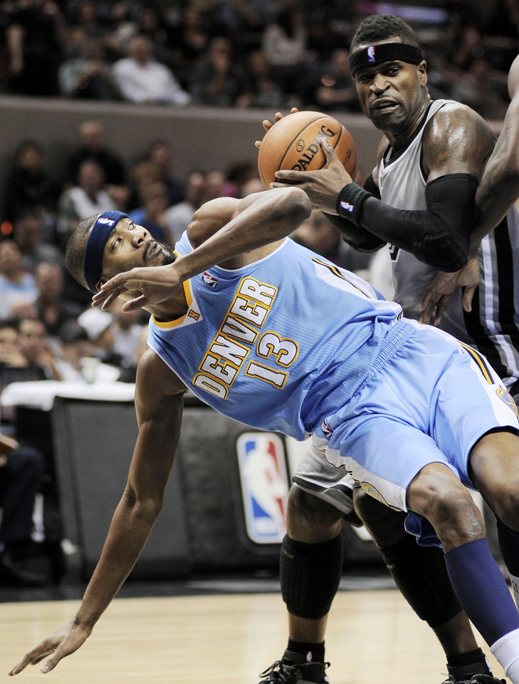 Denver Nuggets\' Corey Brewer (13) falls as he fights San Antonio Spurs\' Stephen Jackson for the ball during the first half of an NBA basketball game, Saturday, Nov. 17, 2012, in San Antonio. (AP Photo/Darren Abate)