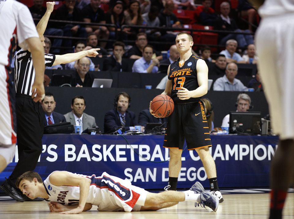 Photo - Oklahoma State's Phil Forte (13) reacts after getting called for a foul on Gonzaga's David Stockton (11) during a second round game of the NCAA men's college basketball tournament at Viejas Arena in San Diego, between Oklahoma State and Gonzaga Friday, March 21, 2014. Gonzaga won 85-77. Photo by Bryan Terry, The Oklahoman