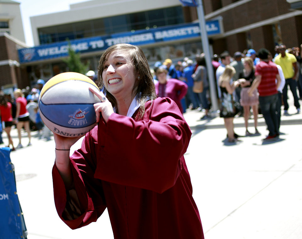 Photo - Dressed in her graduation gown, Katherine Crawford, a graduate of Putnam City North High School, takes a free throw outside the OKC Arena before her commencement at the Cox Convention Center prior to game 7 of the NBA basketball Western Conference semifinals between the Memphis Grizzlies and the Oklahoma City Thunder at the OKC Arena in Oklahoma City, Sunday, May 15, 2011. Photo by John Clanton, The Oklahoman
