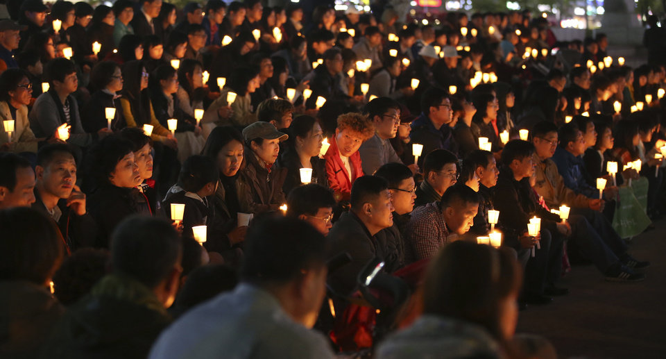 Photo - South Koreans hold candles during a prayer for people believed to have been trapped in the sunken ferry Sewol, in Ansan, South Korea, Monday, April 21, 2014. South Korean President Park Geun-hye said Monday that the captain and some crew members of the sunken ferry committed