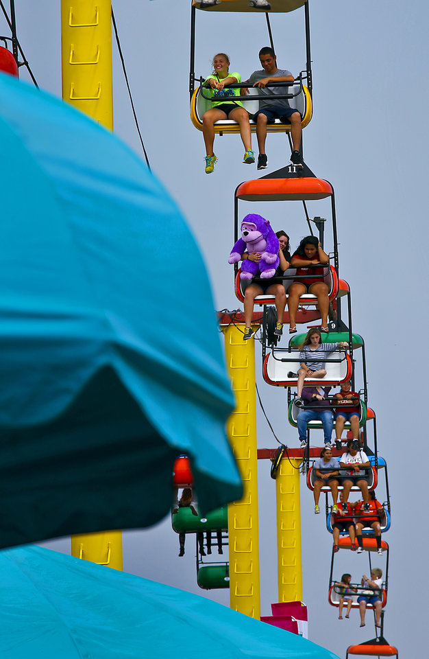 Photo - Visitors to the midway take a ride on the sky tram during the 2013 Oklahoma State Fair on Monday, Sep. 16, 2013. Photo by Chris Landsberger, The Oklahoman