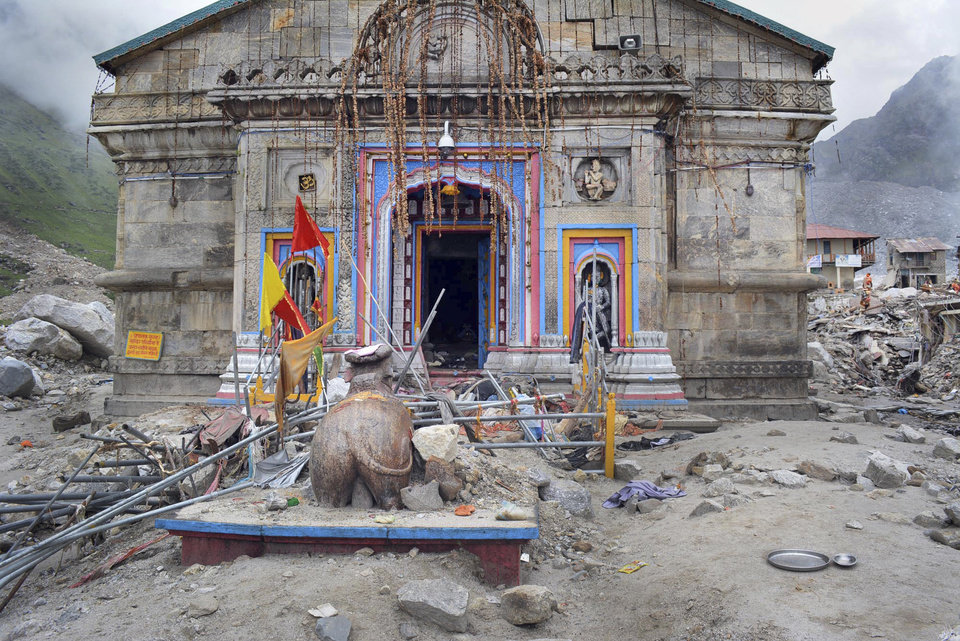 Photo - In this Thursday June 20, 2013 photo, the Kedarnath shrine, one of the holiest of Hindu temples dedicated to Lord Shiva, and other buildings around it are seen damaged following monsoon rains in at Kedarnath  in the northern Indian state of Uttrakhand. A joint army and air force operation are trying to evacuate thousands of people stranded in the upper reaches of the state of Uttrakhand where days of rain had earlier washed out houses, temples, hotels and vehicles leading to deaths of over a hundred people amid fears that the death toll may rise much higher. (AP Photo)