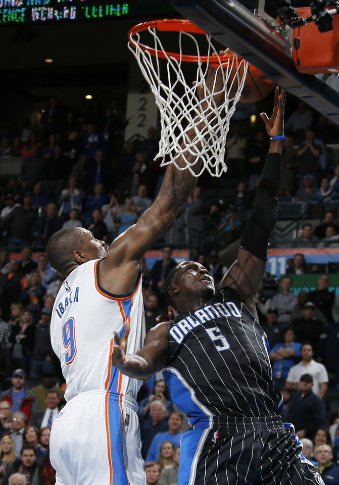 Photo - Oklahoma City's Serge Ibaka (9) blocks the shot of Orlando's Victor Oladipo (5) in the final seconds of an NBA basketball game between the Oklahoma City Thunder and the Orlando Magic at Chesapeake Energy Arena in Oklahoma City, Wednesday, Feb. 3, 2016. Photo by Bryan Terry, The Oklahoman