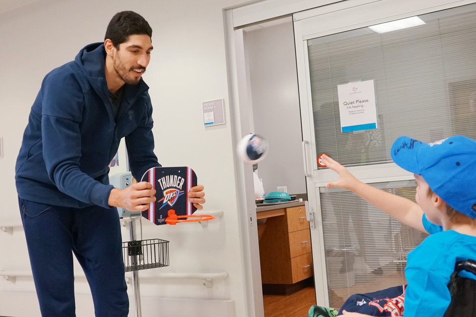 Photo -  Patient Rodney plays basketball with Oklahoma City Thunder center Enes Kanter. [Photo provided by The Children's Center Rehabilitation Hospital]