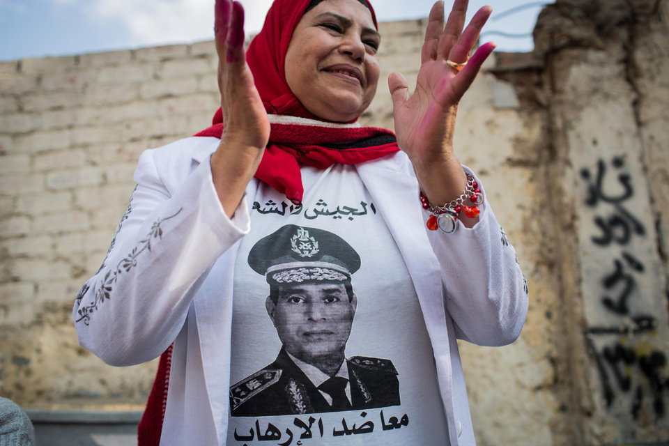 Photo - FILE - In this file photo taken Tuesday, Jan. 14, 2014, an Egyptian woman wears a t-shirt with a photo of Egypt's Defense Minister Gen. Abdel-Fattah el-Sissi outside a polling station on the first day of voting in the country's constitutional referendum in Cairo, Egypt. Former military chief Abdel-Fattah el-Sissi, if he wins Egypt's presidency as is widely expected, will have an overwhelming presence over a shattered political scene. Egypt's once dominant political force, the Muslim Brotherhood, is exhausted under a relentless crackdown. Non-Islamist parties are weak and largely acquiescent to his power. But the political vacuum is hardly a stable one. The Brotherhood is betting that with time the public will turn against el-Sissi. (AP Photo/Eman Helal, File)