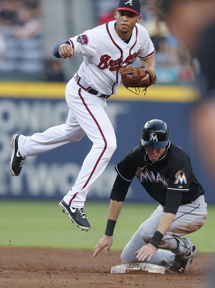 Photo - Atlanta Braves shortstop Andrelton Simmons (19) avoids Miami Marlins' Christian Yelich (21) as he turns a double play on a Donovan Solano ground ball in the third inning of baseball game in Atlanta, Wednesday, July 23, 2014. (AP Photo)