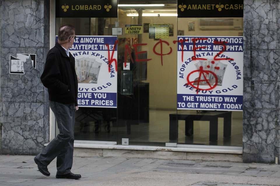 Photo - A man passes a sprayed entrance of a store that buys gold which reads in Greek