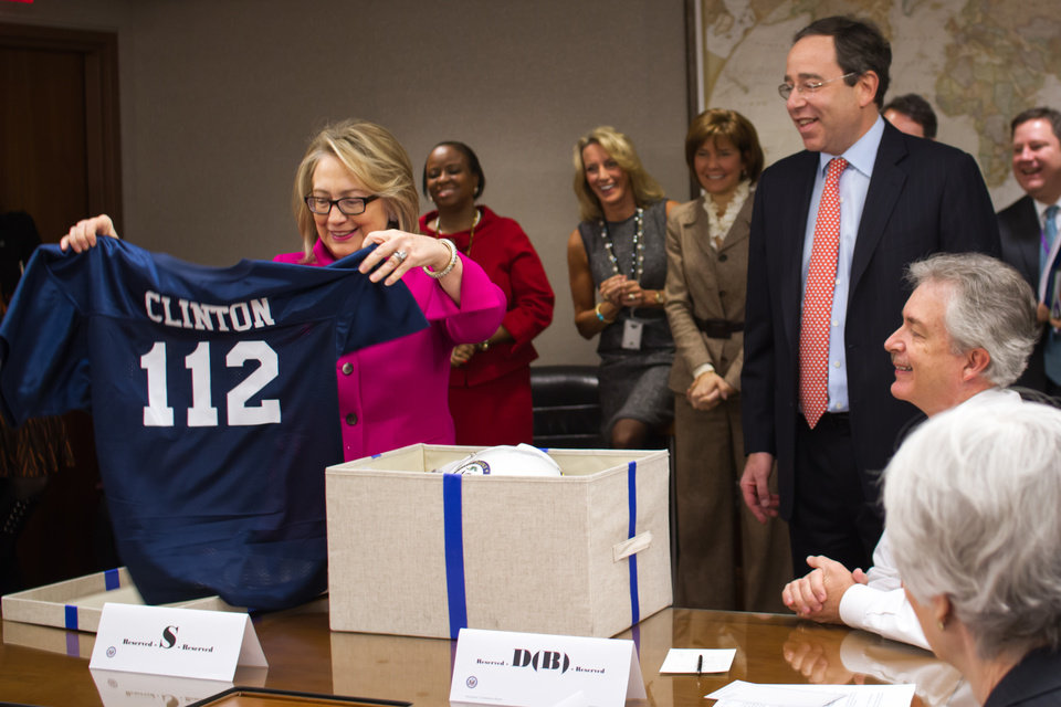 Photo - This handout photo provided by the State Department shows Secretary of State Hillary Rodham Clinton holding up a football jersey, number