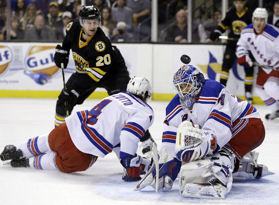 Photo - New York Rangers goalie Henrik Lundqvist (30) keeps the puck out of the net as New York Rangers defenseman Michael Del Zotto (4) defends Boston Bruins left wing Daniel Paille (20) during the second period of an NHL hockey game in Boston, Tuesday, Feb. 12, 2013. (AP Photo/Elise Amendola)