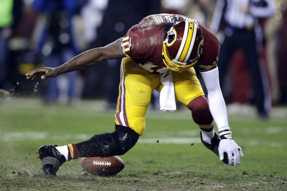 Photo - Washington Redskins quarterback Robert Griffin III twists his knees as he reaches for the loose ball after a low snap during the second half of an NFL wild card playoff football game against the Seattle Seahawks in Landover, Md., Sunday, Jan. 6, 2013. (AP Photo/Matt Slocum)