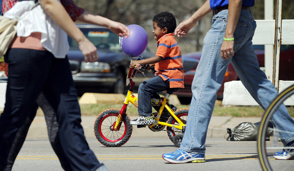 Photo - Stone Badgett, 4, rides his bicycle during the Open Streets OKC event along NW 23rd St. in Oklahoma City, Sunday, March 30, 2014. From noon until 4pm, NW 23rd St. between Robinson and Western was closed to cars for the event. Photo by Nate Billings, The Oklahoman