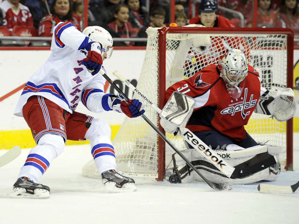 New York Rangers center Dominic Moore, left, tries to get the puck past Washington Capitals goalie Philipp Grubauer (31) during the second period an NHL hockey game, Friday, Dec. 27, 2013, in Washington. (AP Photo/Nick Wass)