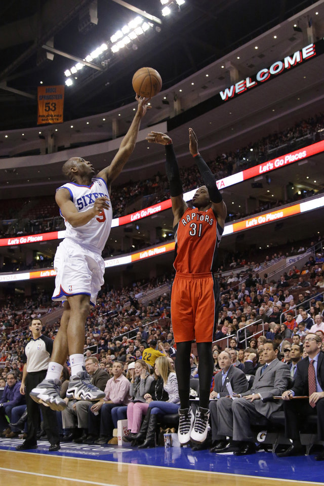 Photo - Toronto Raptors' Terrence Ross, right, has his shot blocked by Philadelphia 76ers' James Anderson during the first half of an NBA basketball game, Friday, Jan. 24, 2014, in Philadelphia. (AP Photo/Matt Slocum)