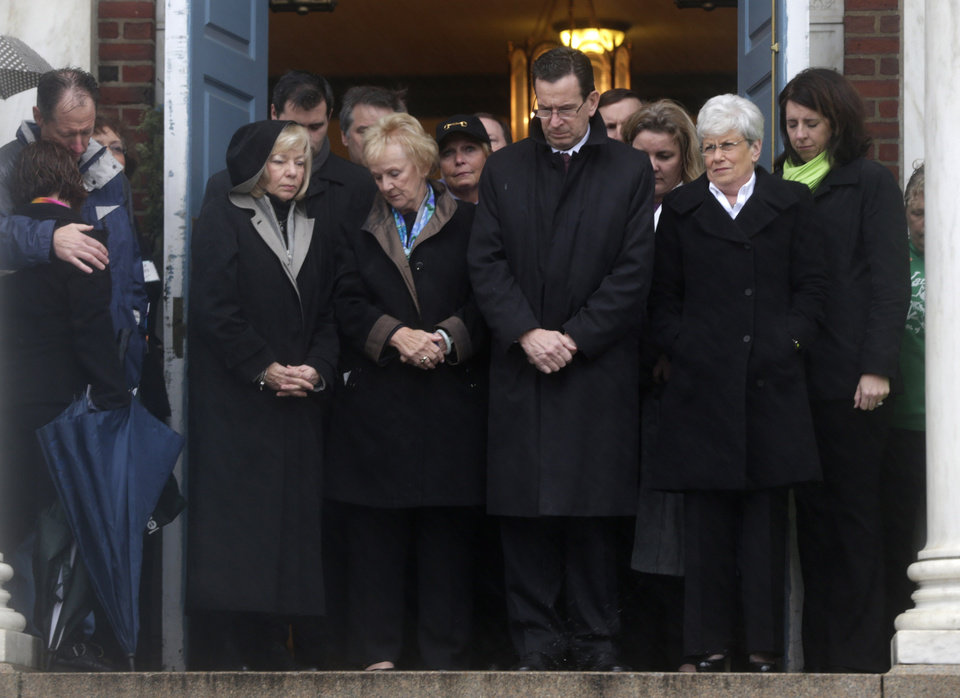 Connecticut Gov. Dan Malloy, center, stands with other officials to observe a moment of silence while bells ring 26 times in Newtown, Conn., Friday, Dec. 21, 2012, in honor of the victims who were killed last Friday during the shooting at Sandy Hook Elementary School. (AP Photo/Seth Wenig)