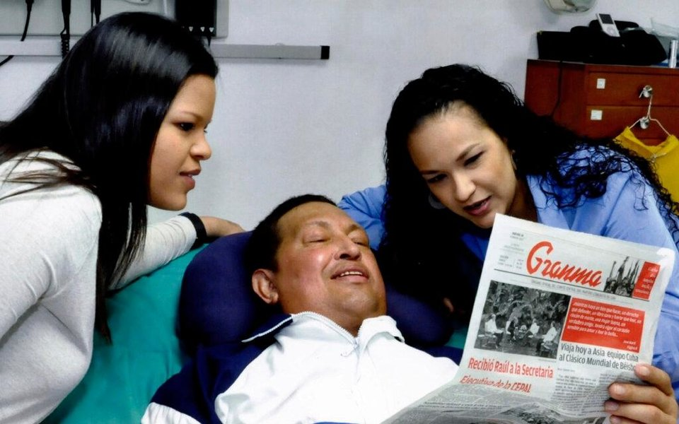 Photo - In this photo released Friday, Feb. 15, 2013 by Miraflores Presidential Press Office, Venezuela's President Hugo Chavez, center, poses for a photo with his daughters, Maria Gabriela, left, and Rosa Virginia as he holds a copy of Cuba's state newspaper at an unknown location in Havana, Cuba, Thursday, Feb. 14, 2013. Chavez remains in Havana undergoing unspecified treatments following his fourth cancer-related operation on Dec. 11. He has hasn't been seen or spoken publicly in more than two months. (AP Photo/Miraflores Presidential Press Office)