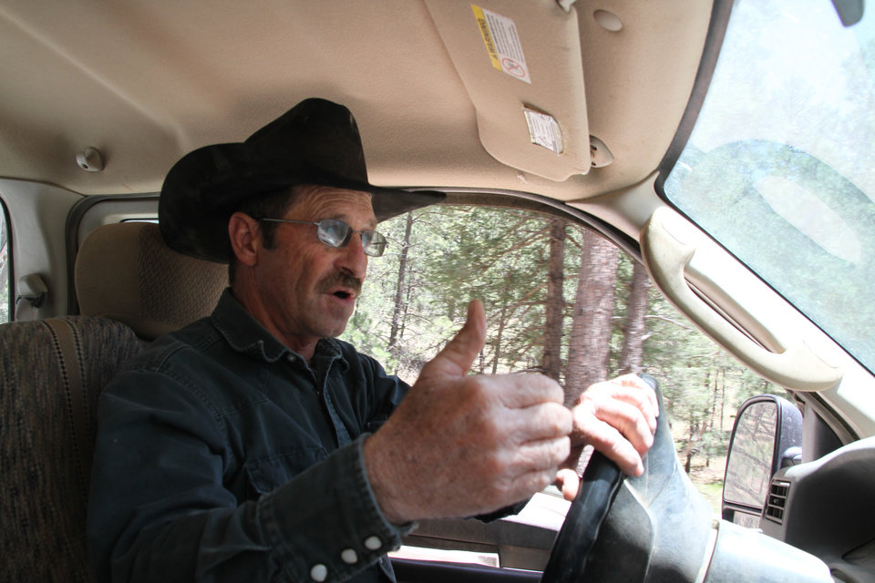 Photo - Otero cattle rancher association president Gary Stone drives his truck in Weed, New Mexico, Thursday, May 15, 2014. The Otero County Cattleman's Association is pitted against the National Forest Service over a fence intended to protect wildlife that the agency installed around a small creek where the ranchers' cattle drink water. (AP Photo/Juan Carlos Llorca)