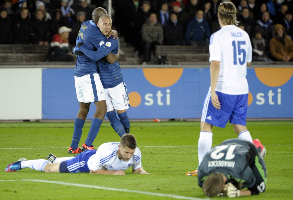 Photo -   France's Jeremy Menez congratulates Abou Diaby, left, after scoring as Finland's Finns Joona Toivio, left on the ground, Markus Halsti, standing no. 15, and goalie Lukas Hradecky react during their World Cup 2014 qualification soccer match in Helsinki, Friday Sept. 7, 2012. (AP Photo/Lehtikuva, Jussi Nukari) FINLAND OUT