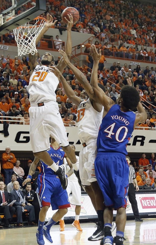 Photo - Oklahoma State 's Michael Cobbins (20) and Marcus Smart (33) battle for a rebound with Kansas' Kevin Young (40) during the college basketball game between the Oklahoma State University Cowboys (OSU) and the University of Kanas Jayhawks (KU) at Gallagher-Iba Arena on Wednesday, Feb. 20, 2013, in Stillwater, Okla. Photo by Chris Landsberger, The Oklahoman
