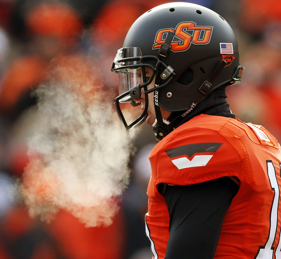 Oklahoma State quarterback Clint Chelf's breath fogs as he stands before a play during the Bedlam college football game between the Oklahoma State University Cowboys (OSU) and the University of Oklahoma Sooners (OU) at Boone Pickens Stadium in Stillwater, Okla., Saturday, Dec. 7, 2013. Photo by Nate Billings, The Oklahoman