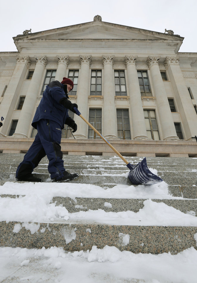 Photo - Nathan Warden, part of the Capitol renovation crew, helps clear snow from the east steps of the State Capitol building in Oklahoma City, Okla. Friday, Jan. 6, 2017.  Photo by Paul Hellstern, The Oklahoman