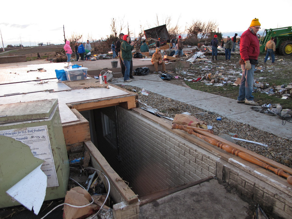 Photo - Friends and neighbors comb the rubble of Curt Zehr's home just outside Washington, Ill., on Sunday, Nov. 17, 2013. Zehr's wife and adult son took shelter in the basement at the base of the pictured stairs as a tornado destroyed their farm house. They were not injured. The tornado cut a path of destruction through Washington. (AP Photo/David Mercer)