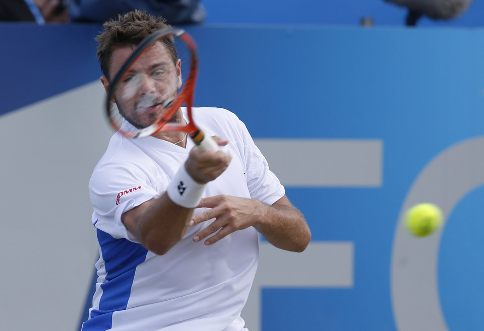 Photo - Stan Wawrinka of Switzerland plays a return to Sam Querrey of U.S. during their Queen's Club grass court championships 3rd round tennis match in London, Thursday, June 12, 2014. (AP Photo/Sang Tan)