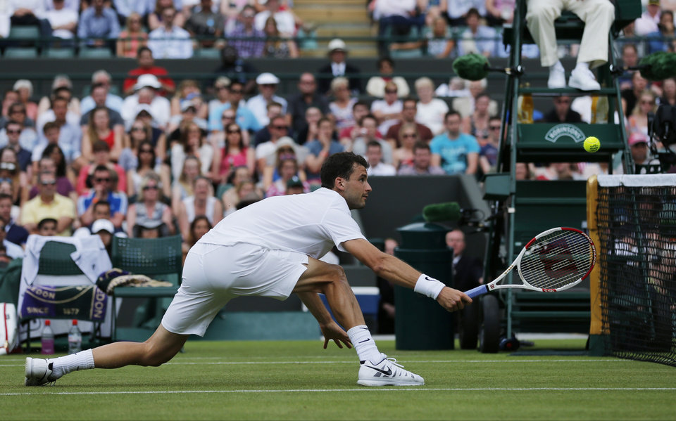 Photo - Grigor Dimitrov of Bulgaria returns to Ryan Harrison of the U.S. during their first round match at the All England Lawn Tennis Championships in Wimbledon, London, Monday, June 23, 2014. (AP Photo/Ben Curtis)