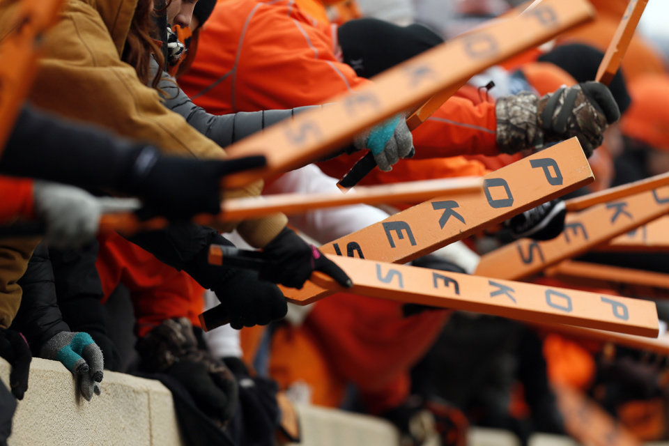Photo - OSU fans hold their paddles during the Bedlam college football game between the Oklahoma State University Cowboys (OSU) and the University of Oklahoma Sooners (OU) at Boone Pickens Stadium in Stillwater, Okla., Saturday, Dec. 7, 2013. OU won, 33-24. Photo by Nate Billings, The Oklahoman