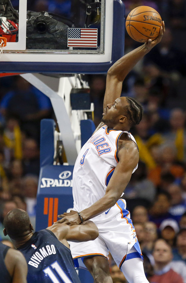Photo - Oklahoma City's Jerami Grant (9) takes the ball to the hoop against Orlando's Bismack Biyombo (11) during an NBA basketball game between the Oklahoma City Thunder and the Orlando Magic at Chesapeake Energy Arena in Oklahoma City, Monday, Feb. 26, 2018. Oklahoma City won 112-105. Photo by Nate Billings, The Oklahoman