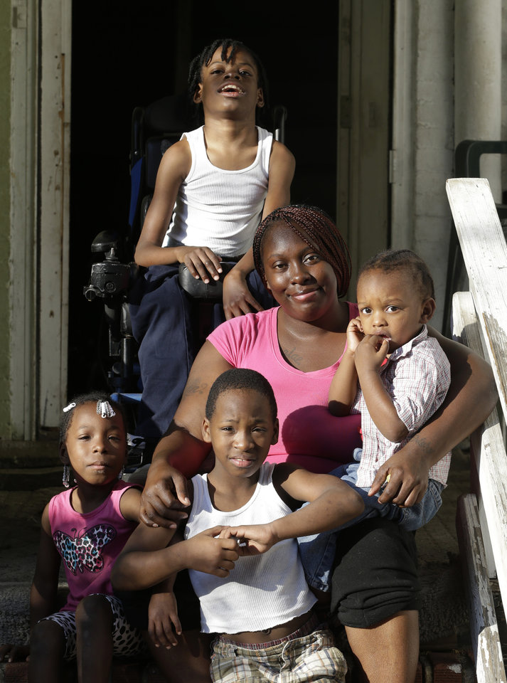 Photo - In a Wednesday, Oct. 2, 2013 photo, Patricia Jones, 34, center, poses for a photo outside of her home in Newark, N.J., with her children, clockwise from top, Nature Harris, 15, Latrell Armstrong, 2, Dashaquan Armstrong, 6, and Pashalae Armstrong, 4. Jones was denied getting a proof printout of Harris' disability to apply for government aid because the shutdown has closed her local social security office. Like millions of other low-income women, Jones relies on the federal Women, Infants and Children program to pay for infant formula _ a program that's now jeopardized by the federal government shutdown. New Jersey and other states say they have enough money to operate the program for another few weeks, but advocates worry what will happen next. (AP Photo/Julio Cortez)