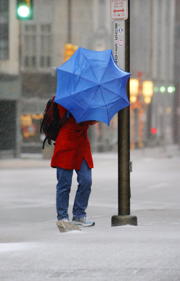 Photo - A pedestrian fights the wind and ice with an umbrella on Robinson Street in downtown Oklahoma City early Thursday morning, Dec. 24, 2009. Photo by Paul B. Southerland, The Oklahoman